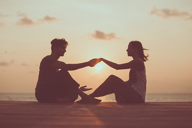 couple holding hands at sunrise